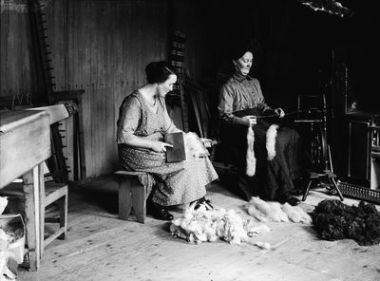 Shetland Spinning and cairding. Andrina Petrie and her mother Barbara Petrie (nee Tait) carding and spinning. Stretchers along wall, large sock brods, Shetland scarf.